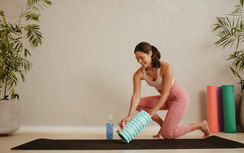 Woman disinfecting exercise roller in fitness studio
