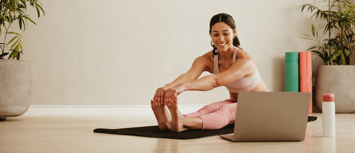 Woman doing yoga watching video on laptop