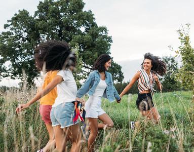 Happy females running on field enjoying summer journey