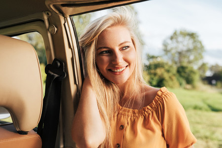 Young cheerful woman with blond hair leaning by a car looking away
