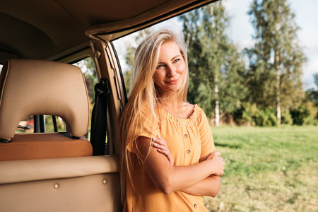 Beautiful blond woman with long hair leaning a van looking away