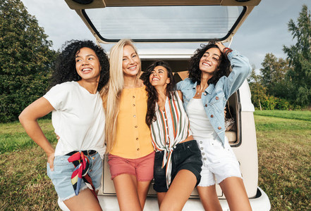 Group of four multi ethnic women standing near a minivan