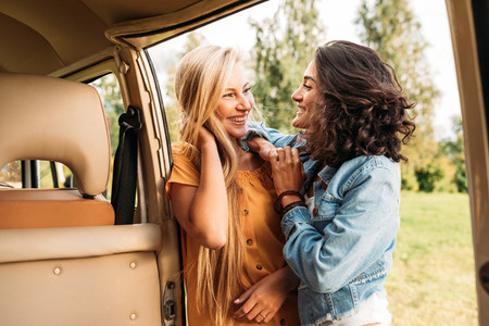 Two young women friends standing at camper van looking at each other