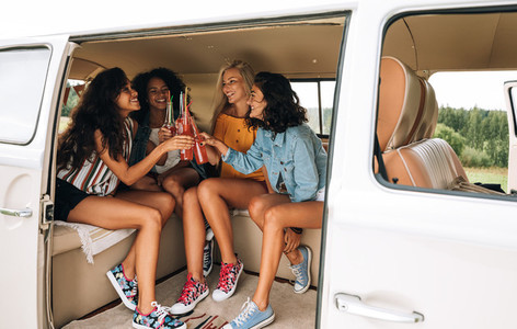 Group of multi ethnic women celebrating during a road trip  Smiling girlfriends cheering with bottles in a minivan