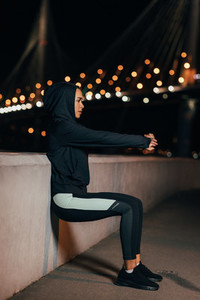 Side view of a young fit woman doing wall squat  Sportswoman doing wall sit at night