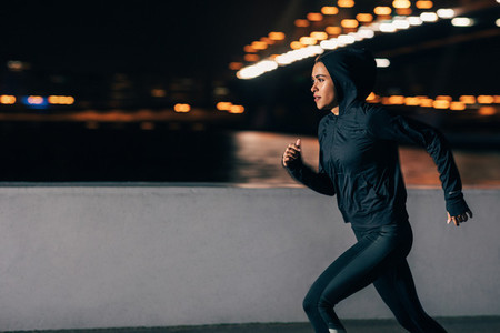 Side view of a woman in hoodie running at night  Middle east female jogger exercising outdoors