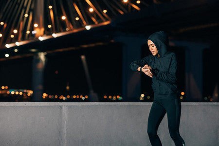 Young sportswoman looking at smartwatch while running at night outdoors
