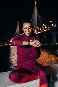 Smiling woman in sportswear sitting at night against bridge checking activity tracker