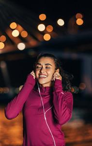 Female runner listening to music on earphones at night