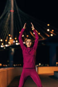 Female athlete in front of bridge at night  Woman wearing sportswear warming up body in the city in the evening