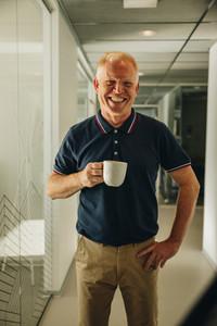 Happy senior businessman having coffee