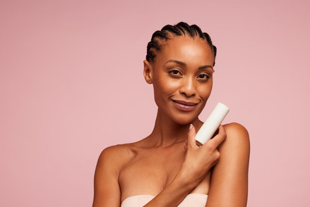 Beautiful woman presenting skincare product