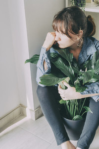 portrait of a woman sits on the floor and hugs a plant