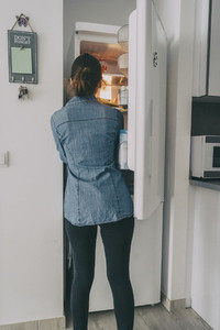 girl inside the kitchen opening the fridge door