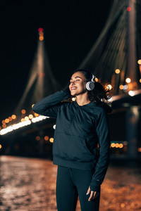 Smiling sportswoman relaxing during fitness training at night