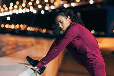 Fit woman stretching her body during a workout at night