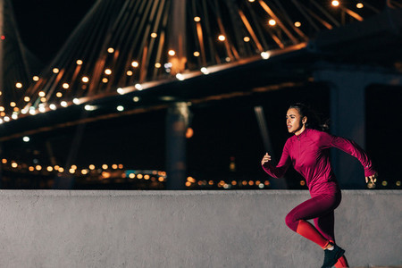 Woman running at night on embankment  Side view of female jogger sprinting outdoors against bridge