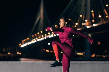 Fit woman doing warming up exercises at night outdoors