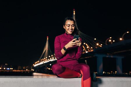 Smiling sportswoman sitting on an embankment using smartphone at night