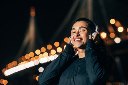 Happy woman wearing white wireless headphones listening to music with closed eyes