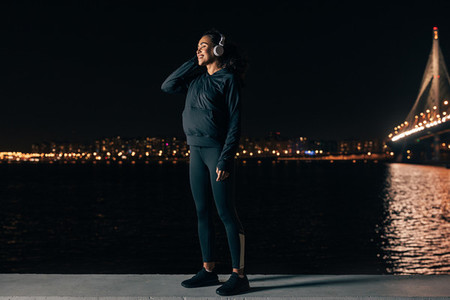 Young female in sport clothes standing on embankment listening to music against night city lights