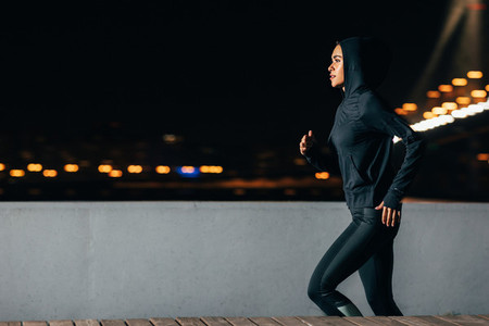 Side view of young female jogger exercising outdoors at night  Woman running along the embankment