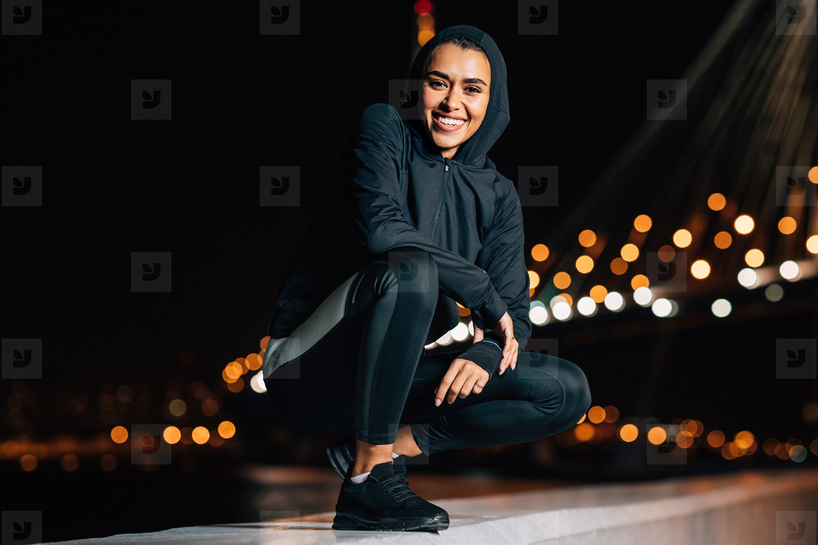 Cheerful middle east woman in sport hoodie shirt sitting outdoors at night looking at camera