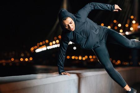 Female in hooded sport shirt exercising outdoors