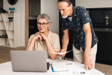 Senior caucasian couple calculating bills at home  Two mature people looking at laptop and managing finances