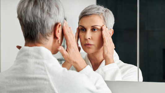 Mature woman in a bathroom in front of a mirror touching head with hands