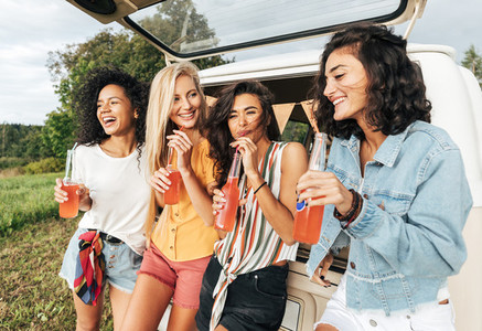 Group of four female friends celebrating during road trip standing at minivan