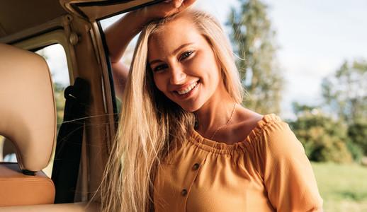 Young cheerful woman looking at camera while standing at a minivan