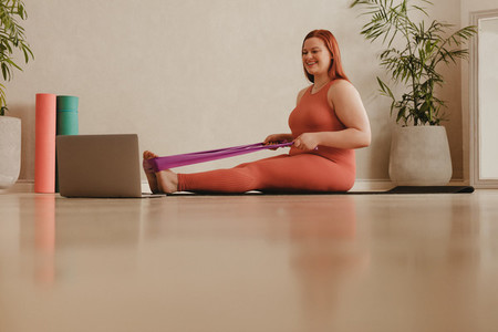 Fit woman watching video and doing stretching workout