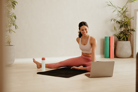 Woman attending online fitness class for exercising at home