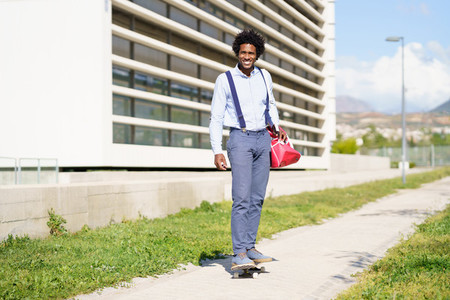 Black businessman riding skateboard near office building