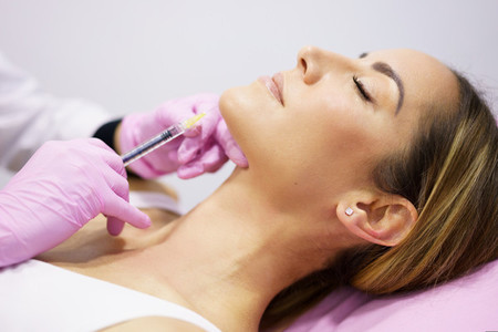 Doctor injecting hyaluronic acid into the ching of a woman as a facial rejuvenation treatment