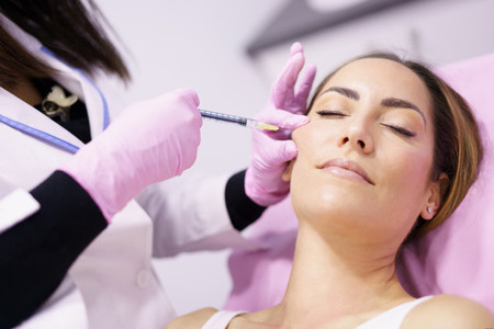 Doctor injecting hyaluronic acid into the cheekbones of a woman as a facial rejuvenation treatment