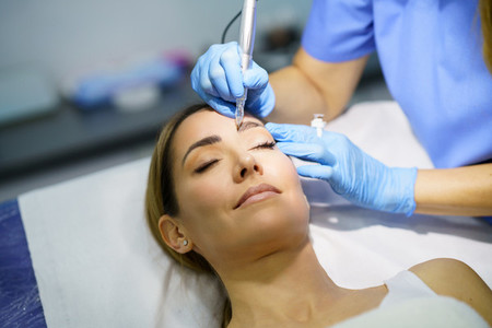 Permanent make up for eyebrows of beautiful woman in a beauty salon  Micropigmentation treatment