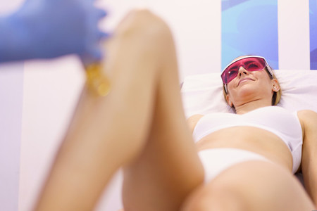 Woman receiving legs laser hair removal at a beauty center