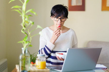 Woman eating strawberries while teleworking from home on her laptop