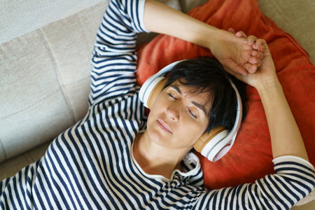 Middle aged woman listening to soothing music with headphones lying on her sofa