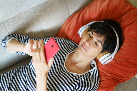 Woman consulting her smartphone while listening to music with headphones lying on the sofa