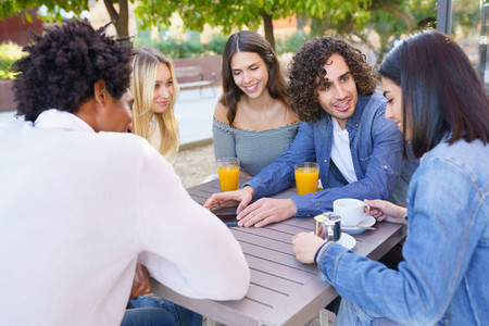 Multi ethnic group of friends having a drink together in an outdoor bar