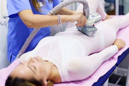 Woman in special suit having a anti cellulite belly massage with spa apparatus