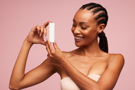 Happy african woman holding a cosmetic product