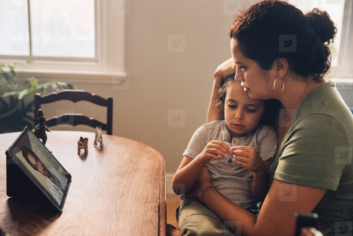 Mother taking online consultation from a doctor on her son sickn