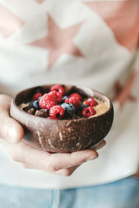 Woman holding healthy breakfast bowl with oats and fruits