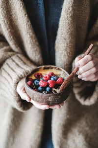 Healthy vegan breakfast bowl with oats  berries in womans hands