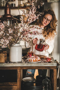 Woman pouring tea to cups over table with bundt cake