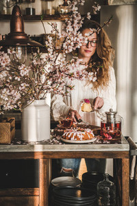Woman serving homemade gluten free bundt cake near blooming branches